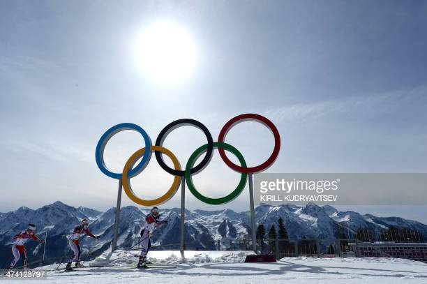 Gold medalist Norway's Marit Bjoergen bronze medalist Norway's Kristin Stoermer Steira and silver medalist Norway's Therese Johaug ski past the rings...