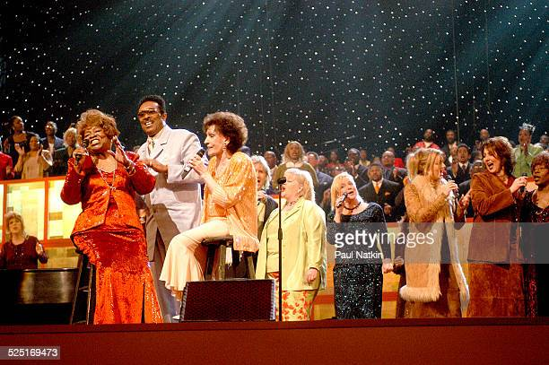 From left gospel musicians Albertina Walker unidentified and Dottie Rambo perform onstage with a large choir Dallas Texas March 11 2003