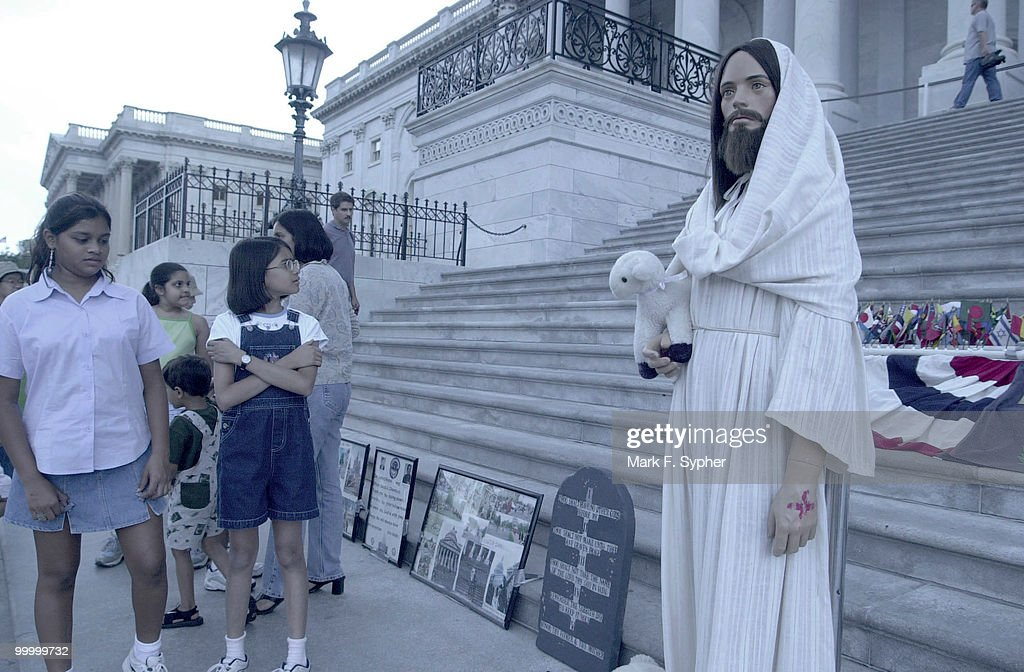 From left, Hetashree Jangla, 11, of Atlanta, GA., and Sneha Shah, 11, of Raleigh, N.C., are surprised to see Jesus on the back steps of the Capital. The shrine is now in its' 23rd year of display, says owner Rita Warren, of Fairfax, VA. Warren displays the statue and its' surrounding memorabilia to 'show foreigners that we do really have the freedom to express faith and speech.'