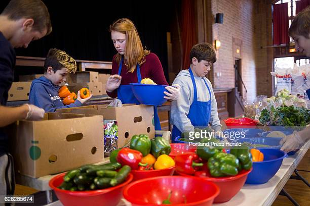 From left Isaac Small Calvin Small Genevieve Depke William Depke and Dan Haskell work together to set up the groceries that patrons can take home...
