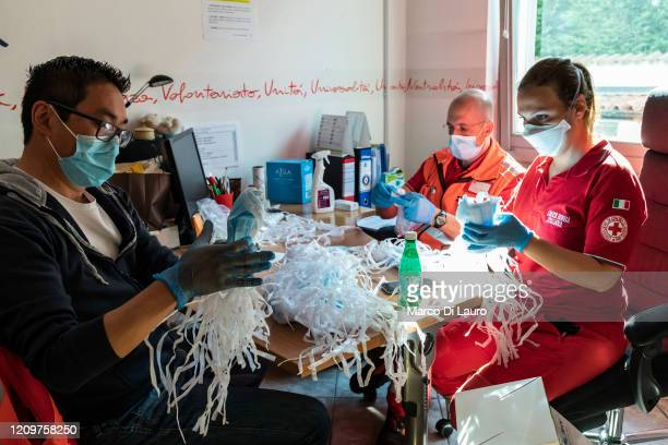 From left, Italian Red Cross members Andrea Romano, Federico Donarini and Antonella Matta pack protective masks in 10-piece bags to distribute to the...