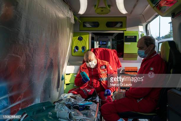 From left Italian Red Cross members Marco Pezzotta and Stefano Spinedi check and prepare the ambulance before their shift on April 5 2020 in Bergamo...