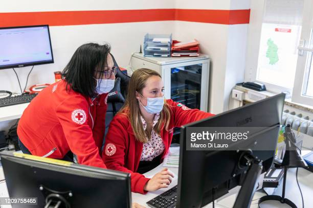 From left Italian Red Cross members Paola Rota and Alice Carobbio work on the switchboard answering calls on April 4 2020 in Bergamo Italy The number...