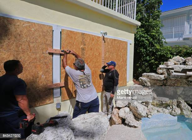 From left JC Abreu Peter Gonzalez and Jorge Abreu with Hurricane Busters Enterprises install hurricane shutters at a home in Key Largo in preparation...