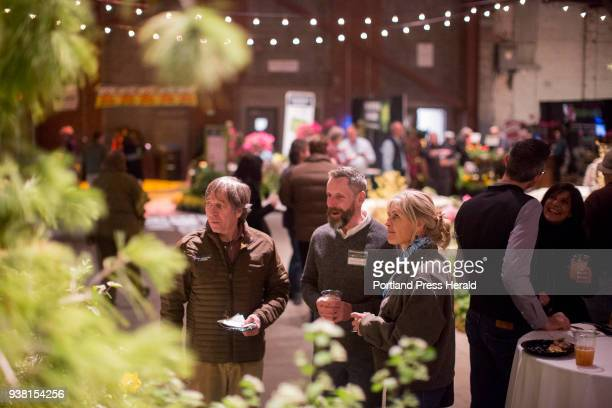 From left Jeff Tarling Timothy Bate and Jan Conley chat in front of one of the many garden displays at the 2018 Maine Flower Show at Thompson's Point