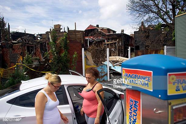 From left, Jessica Soto and Tanazane Montesdeoca vacuum their car in front of an arson attack on row houses behind them on August 14, 2016 in...