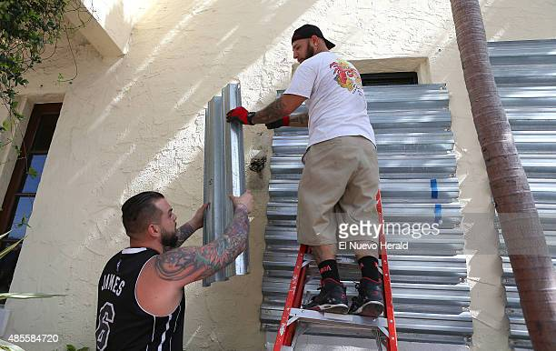 From left Joe's Stone Crab employees Jordan Garcia and Manny Cortes installing shuttles in preparation for Tropical Storm Erika on Friday August 28...
