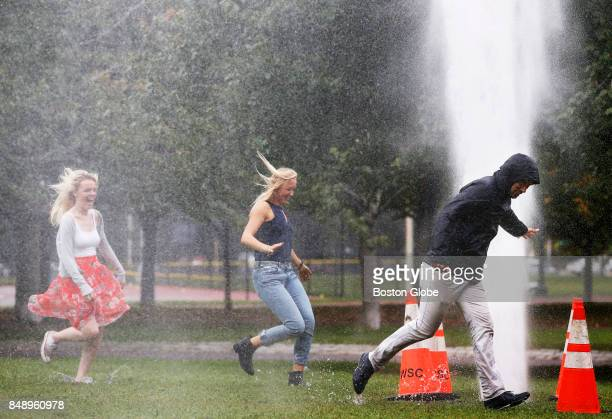 From left Katie O'Flaherty of Ireland Jennifer Marsh of Michigan and Luis Antonio Gonzalez run into a plume of water spouting up into the air on the...