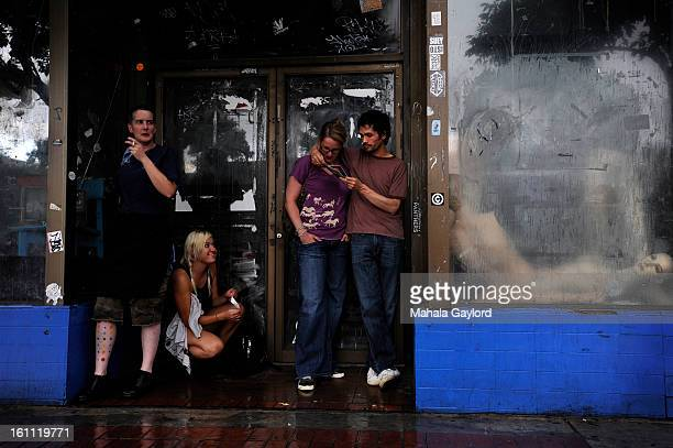 DENVER COJULY 22 2010 From left Kelly Sunshine Faison Alexa Schoeman Jen and John Mix get shelter from the rain as they wait for the Underground...