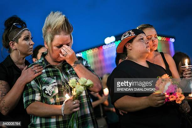 From left Kyra Murphy wife Crystal Murphy and Nicole Edwards and her wife Kellie Edwards observe a moment of silence during a vigil outside the Dr...
