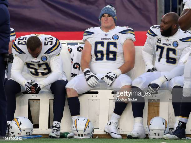 From left Los Angeles Chargers' Mike Pouncey guard Dan Feeney and tackle Russell Okung sit on the bench in the fourth quarter The New England...