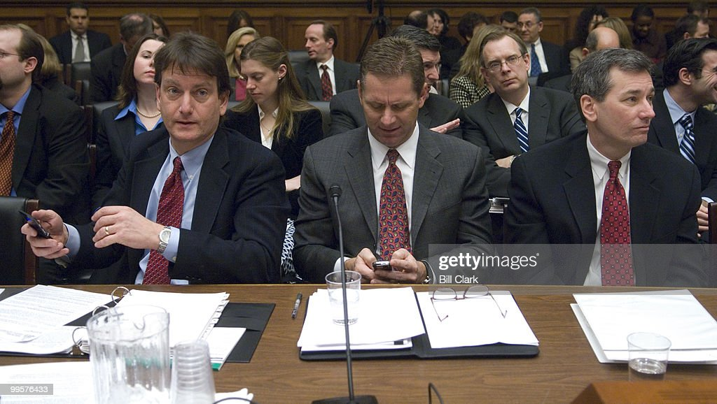 From left, Marc Rotenberg, executive director of the Electronic Privacy Information Center, and former Rep. Steve Largent, R-Okla., president and CEO of CTIA-The Wireless Association, check their cell phones as Walter McCormick, president and CEO of the United States Telecom Association, looks on before the start of the House Energy and Commerce Committee hearing on 'Combating Pretexting: H.R.936, Prevention of Fraudulent Access to Phone Records Act' on Friday, March 9, 2007.