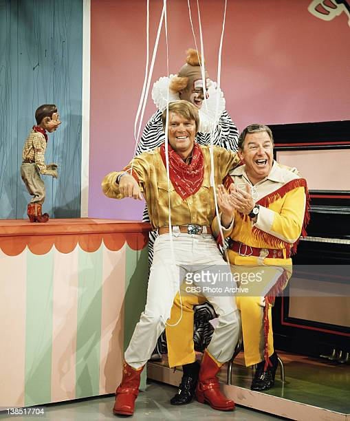 From left marionette Howdy Doody Clarabell the Clown Glen Campbell sitting on the knee of Buffalo Bob Smith in a comedy skit on The Glen Campbell...