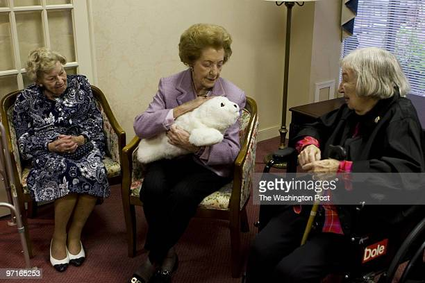 From left Mary Crutcher Ida Mary Boyd 86 and Rebecca Dole sit with Paro the robot baby harp seal a Sept 25 2008 in McLean VA at Vinson Hall...