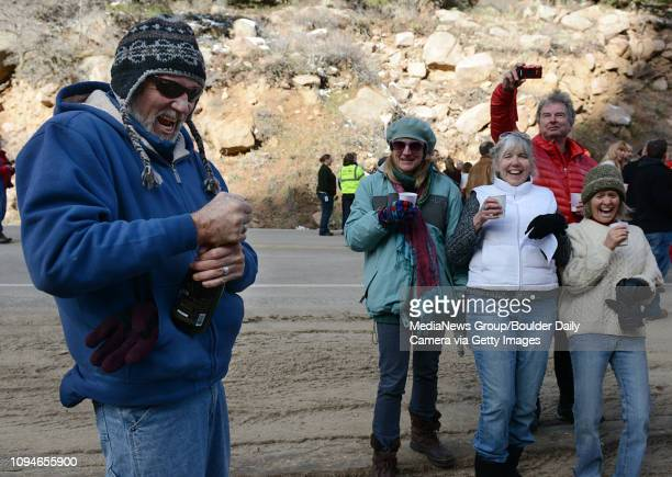 Mike Dowell struggles to open a bottle of champagne as fellow Allenspark residents Christine Futro Sharon Arms Andrew Griffiths and Peggy Donahue...