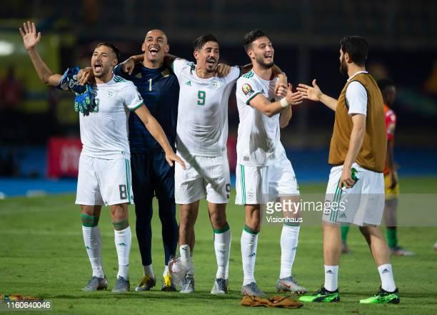 From left Mohamed Belaili Izzeddine Doukha Baghdad Bounedjah Rami Bensebaini and Rafik Halliche of Algeria celebrate winning the 2019 Africa Cup of...