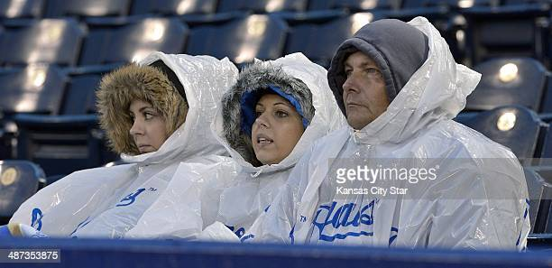 From left Nikki Van Trump sister Courtney Van Trump and their father Ray Van Trump wait out a rain delay as the Kansas City Royals play host to the...