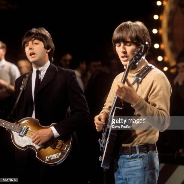 From left, Paul McCartney and George Harrison of English rock and pop group The Beatles perform together on stage during rehearsals for the ABC...