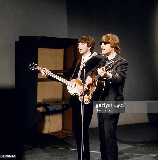 From left, Paul McCartney and John Lennon of English rock and pop group The Beatles perform together on stage for the American Broadcasting Company...