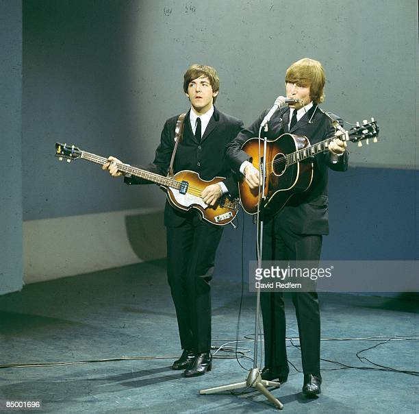 From left Paul McCartney and John Lennon of English rock and pop group The Beatles perform on stage for the American Broadcasting Company music...