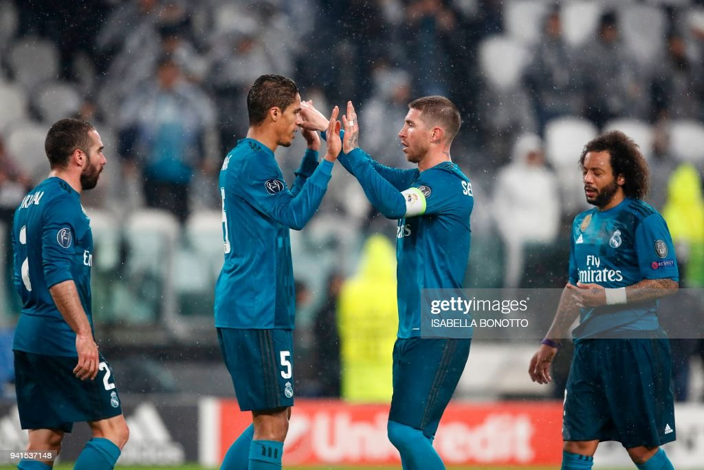 Real Madrid's Spanish defender Dani Carvajal, Real Madrid's French defender Raphael Varane, Real Madrid's Spanish defender Sergio Ramos and Real Madrid's Brazilian defender Marcelo celebrate at the end of the UEFA Champions League quarter-final first leg football match between Juventus and Real Madrid at the Allianz Stadium in Turin on April 3, 2018. Ronaldo scores twice as Real Madrid beat Juventus 3-0. / AFP PHOTO / Isabella BONOTTO