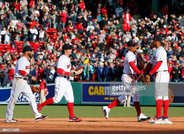 From left Red Sox Dustin Pedroia Andrew Benintendi and Mookie Betts shake hands with Xander Bogaerts as they celebrate their win against the Pirates...