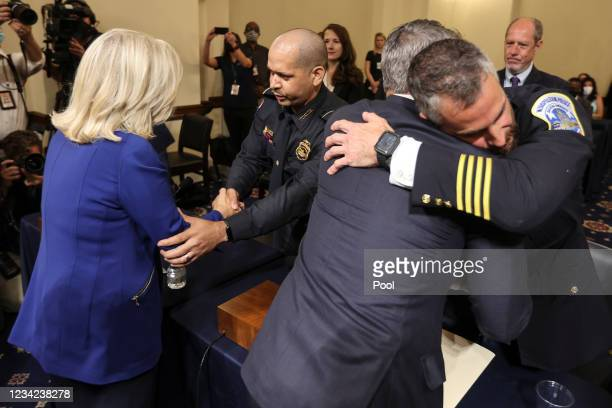 From left, Rep. Liz Cheney, R-WY, greets Sgt. Aquilino Gonell as Representative Adam Kinzinger, R-IL, embraces U.S. Capitol Police, Michael Fanone as...