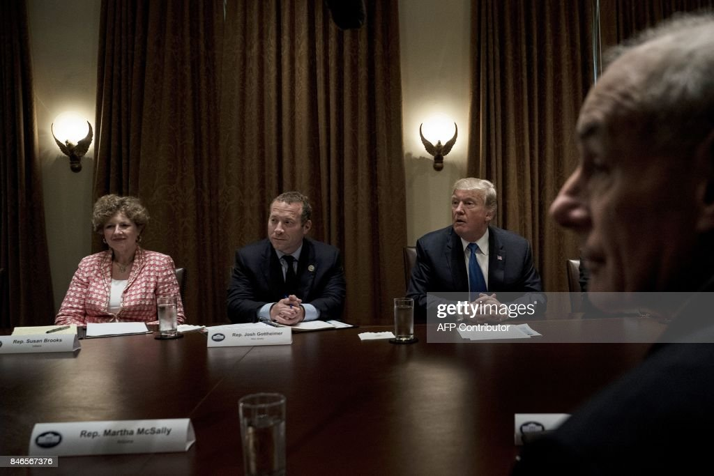 Rep. Susan Brooks (Republican from Indiana), Rep. Josh Gottheimer (Democrat from New Jersey -L), US President Donald Trump and White House Chief of Staff John Kelly wait for a meeting with lawmakers in the Cabinet Room of the White House on September 13, 2017 in Washington, DC. / AFP PHOTO / Brendan Smialowski