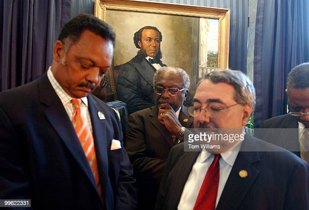 From left, Rev. Jesse Jackson, Reps. Jim Clyburn, G.K. Butterfield, D-N.C., and Bobby Rush, D-Ill., bow their heads in prayer after the portrait of...