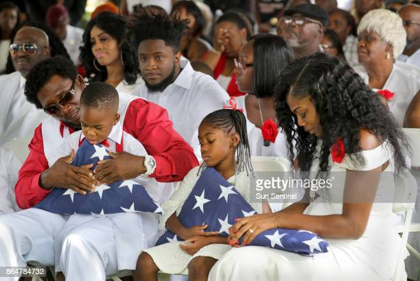 From left Richard Johnson Sr holds La David Johnson Jr Ah'Leesya Johnson and Myeshia Johnson the wife of Army Sgt La David Johnson during his burial...