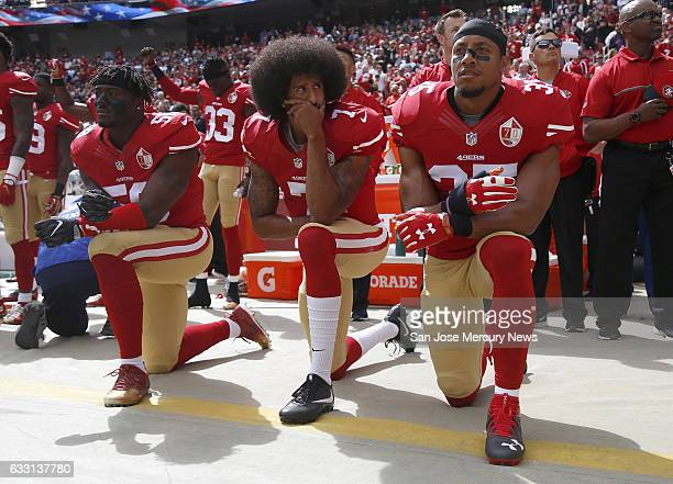 From left San Francisco 49ers Eli Harold quarterback Colin Kaepernick and Eric Reid kneel during the national anthem before their NFL game against...