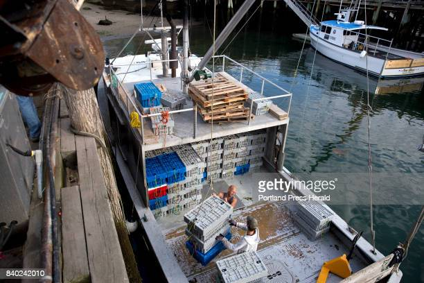 From left Scott Clark and Thomas Kunn of Fox Island Lobstering help unload unioncaught lobster from Vinalhaven off of their smack boat to load onto a...