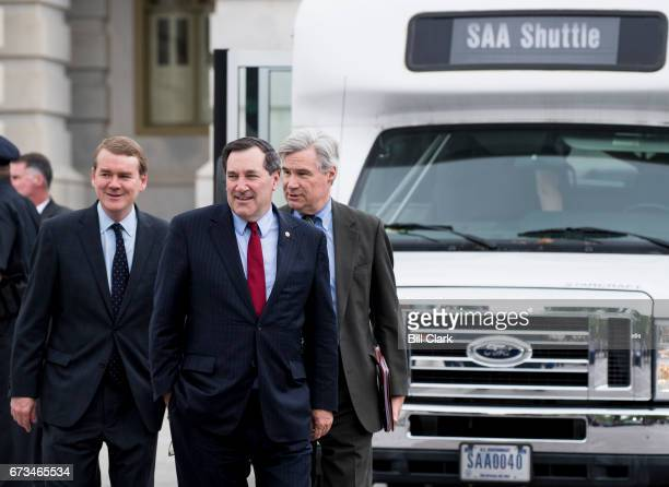 From left Sen Michael Bennet DColo Sen Joe Donnelly DInd and Sen Sheldon Whitehouse DRI arrive to board a bus transporting Senators to a briefing on...