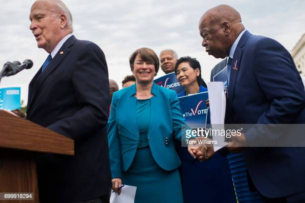 From left Sens Patrick Leahy DVt left Amy Klobuchar DMinn center and Rep John Lewis DGa right attend a news conference on the East Front lawn to...