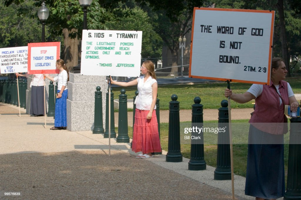 From left, Shanna Carpenter, her sister Shaeila Carpenter, and their mother Shirley Carpenter, all of West Virginia, hold large signs protesting proposed Senate hate crimes legislation during a rally in Upper Senate Park on Tuesday morning, July 10, 2007. They were part of a rally organized by Repent America. The group will hold a press conference to adress what they see as a trend seeking to criminalize Christianity in America.