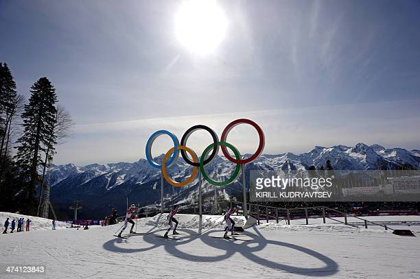 Silver medalist Norway's Therese Johaug bronze medalist Norway's Kristin Stoermer Steira and gold medalist Norway's Marit Bjoergen ski past the rings...