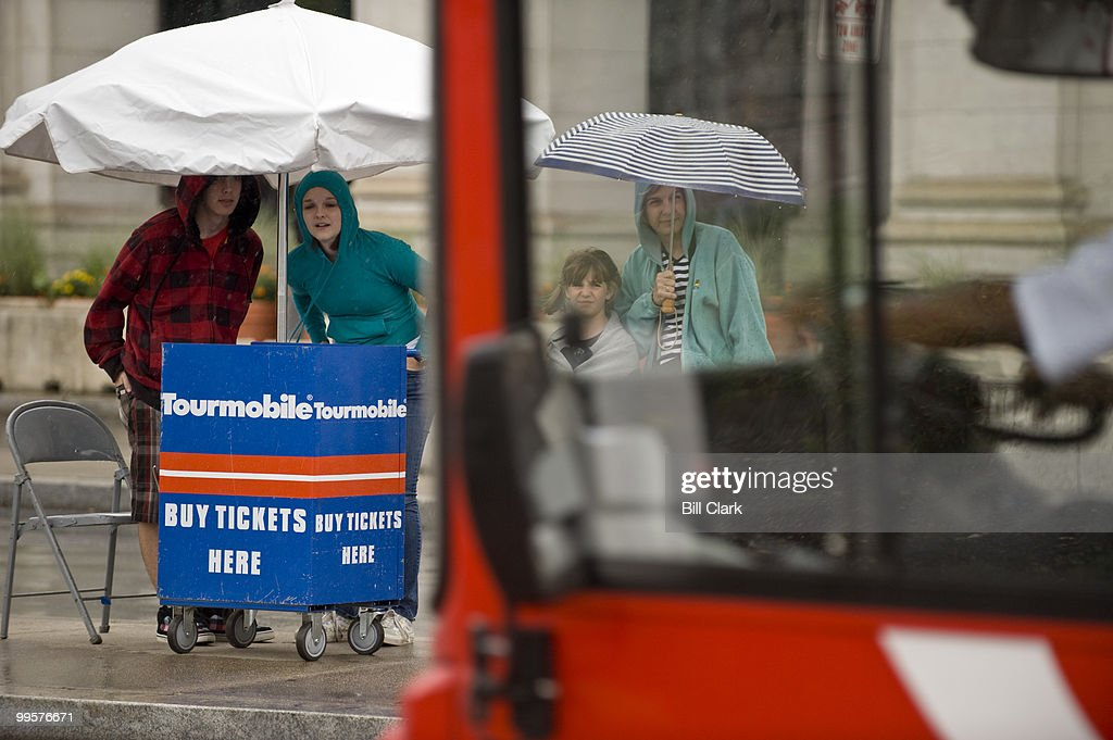 From left, Steven Lane, 17, Stephanie Brownell, 17, Shelby Lane, 7, and her mother Gail Lane, of Warrenton, Va., try to keep dry as they wait for the next Tourmobile to pick them up outside of Union Station on Wednesday, June 17, 2009.