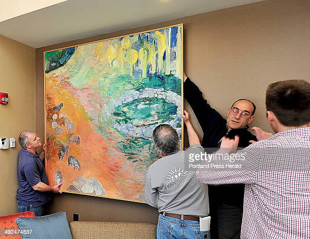 From left, Tim Grobbin and Andrew Roberts hold a painting by Alison Haldreth of Portland as Jack Soley gets help from Todd Dominski, right, as local...