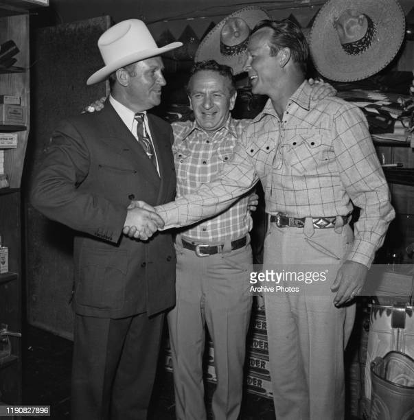 From left to right, actor and singer Gene Autry , tailor Nudie Cohn and actor and singer Roy Rogers at a party for Cohn and various Western stars,...