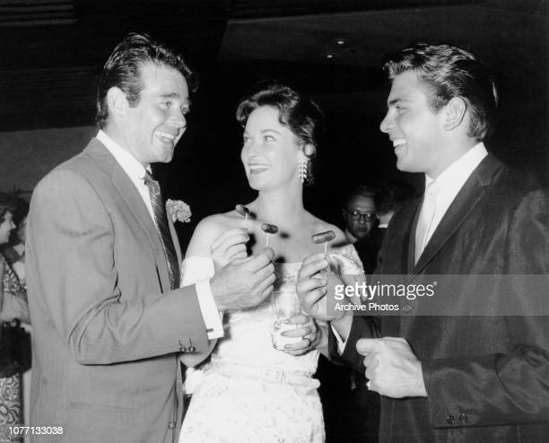 From left to right actor Stuart Whitman and his wife Patricia with Fabian eating hot dogs on sticks at a party thrown by acting couple Fernando Lamas...