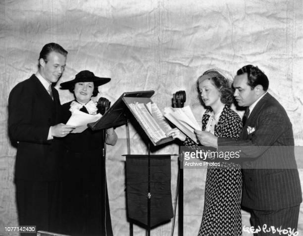 From left to right actor Wayne Morris columnist Louella Parsons Bette Davis and Edward G Robinson make a studio recording circa 1937 Robinson Davis...