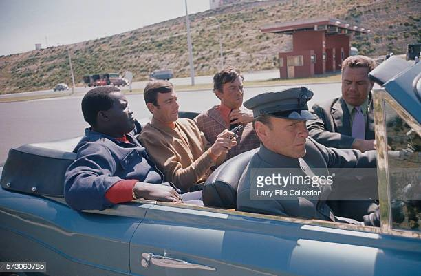 From left to right actors Irvin Allen George Lazenby and Geoffrey Cheshire on the set of the James Bond film 'On Her Majesty's Secret Service' on...