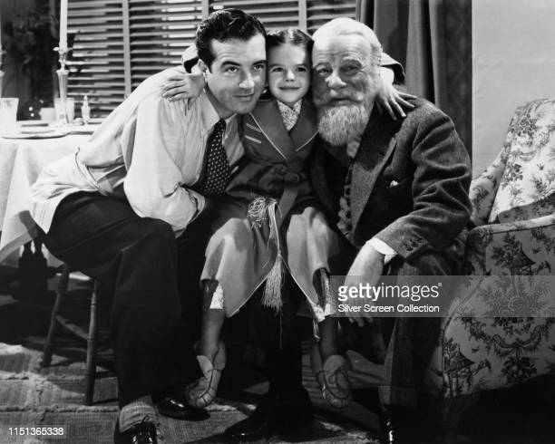 From left to right actors John Payne as Fred Gailey Natalie Wood as Susan Walker and Edmund Gwenn as Kris Kringle in the film 'Miracle on 34th...