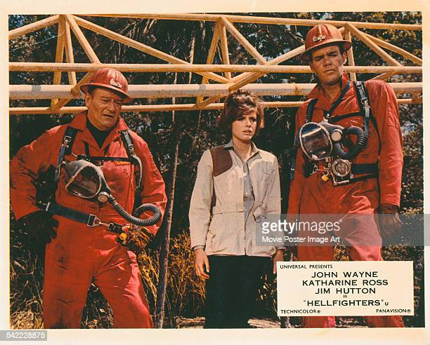 From left to right actors John Wayne Katharine Ross and Jim Hutton appear on the poster for the Universal Pictures film 'Hellfighters' 1968