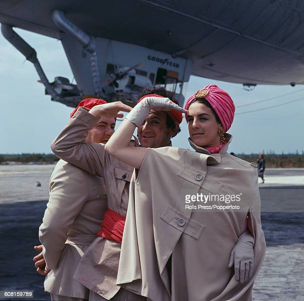 From left to right actors Leo McKern John Bluthal and Eleanor Bron posed together in costume in front of a Goodyear blimp during filming of the...