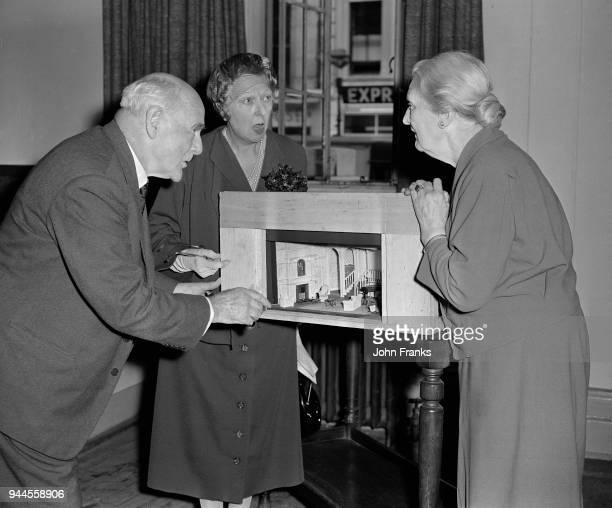 From left to right, actors Lewis Casson , Marie Lohr and Sybil Thorndike discuss a model of the set for the Noël Coward play 'Waiting In The Wings'...