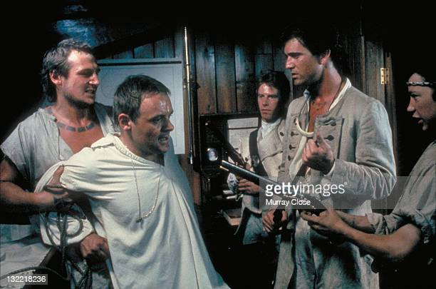From left to right actors Liam Neeson Anthony Hopkins Philip Davis Mel Gibson and Dexter Fletcher in a scene from the film 'The Bounty' 1984