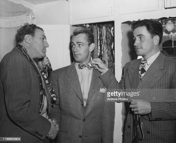 From left to right, actors William Bendix, Alan Ladd and Noah Beery Jr. Trying on ties, 24th January 1943.