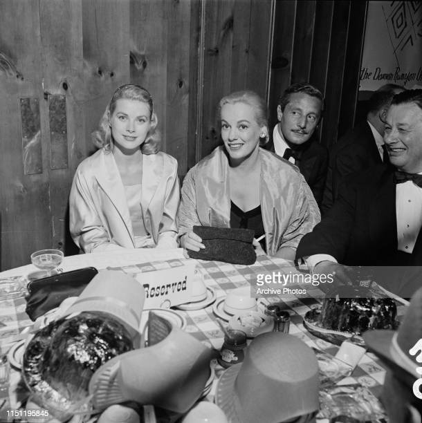 From left to right actress Grace Kelly Faye Emerson Oleg Cassini and restauranteur Bernard 'Toots' Shor at a party for the Damon Runyon Theater at...
