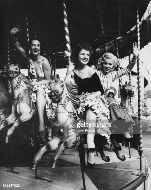 From left to right actresses Angela Lane Barbara Roscoe and June Cunningham take a ride on the merrygoround at the Battersea Fun Fair in London 10th...
